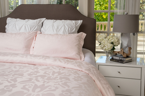 A bed with the pink Mariposa duvet set